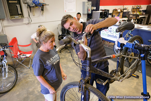 Sustainable transportation advocate and bike shop mechanic Steve Valliant teaches a workshop attendee how to maintain her bicycle.